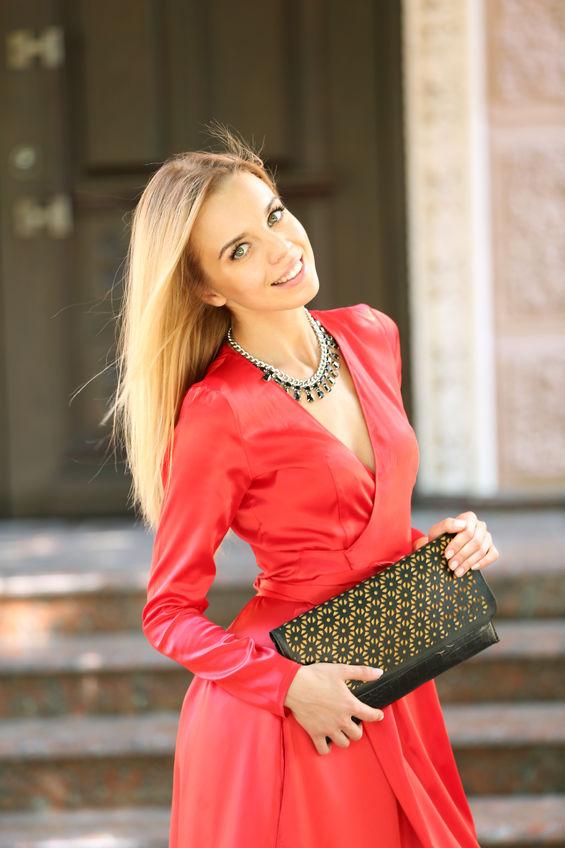 Kobieta w czerwonej sukienkce z naszyjnikiem