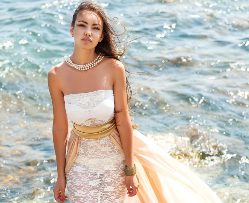 kobieta w białej sukni w morzu z naszyjnikim z pereł