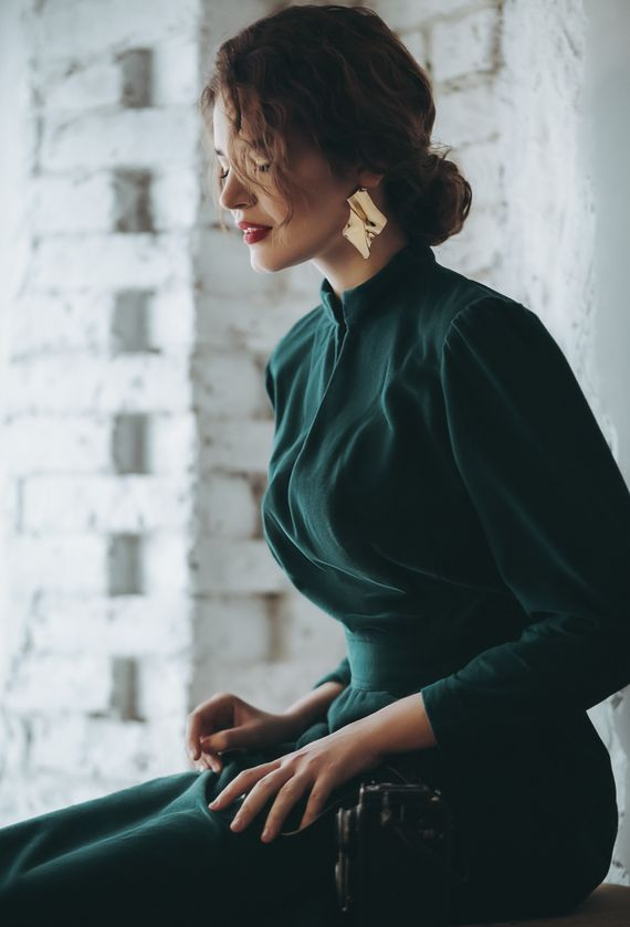 Kobieta w zielonej sukience ze złotymi kolczykami